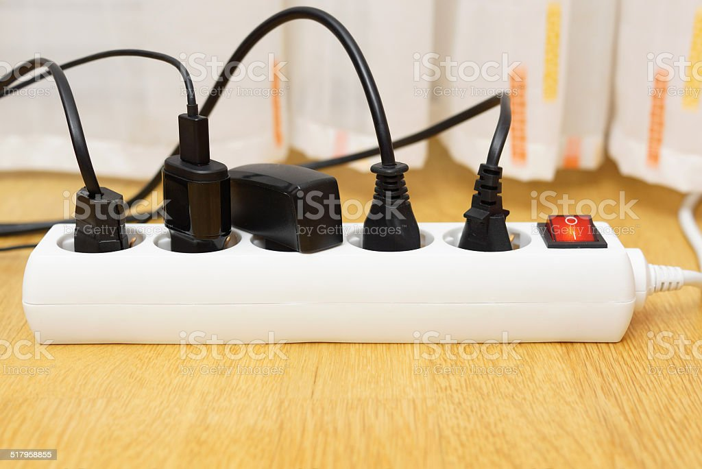 many electrical appliances pluged in surge protector. Power consuption concept stock photo