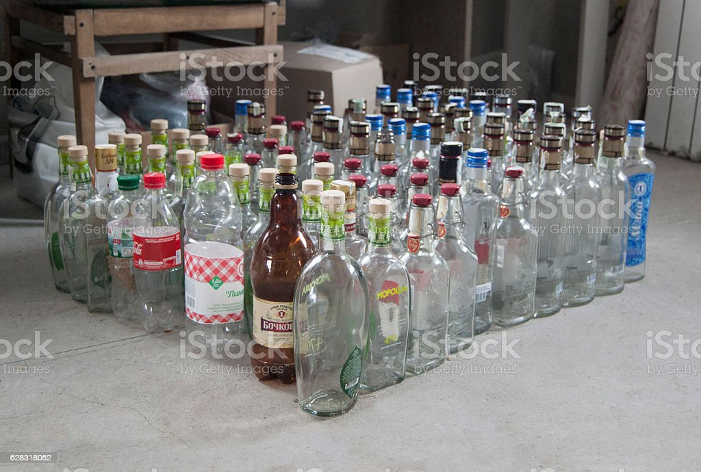 Many empty bottles arranged in room. Alcohol. stock photo