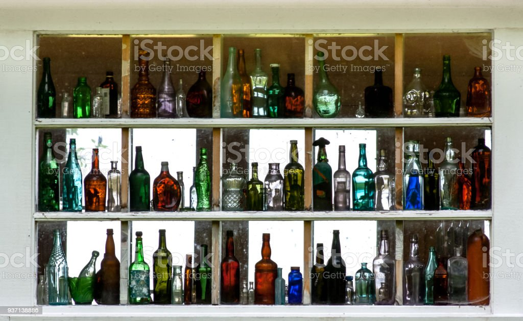 Many empty colorful glass bottles displayed inside a window in rows stock photo