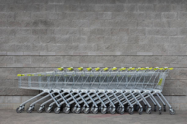 Many empty shopping trolleys with yellow handle standing in a row in the centre of photo at gray brick background of supermarket with copyspace. stock photo