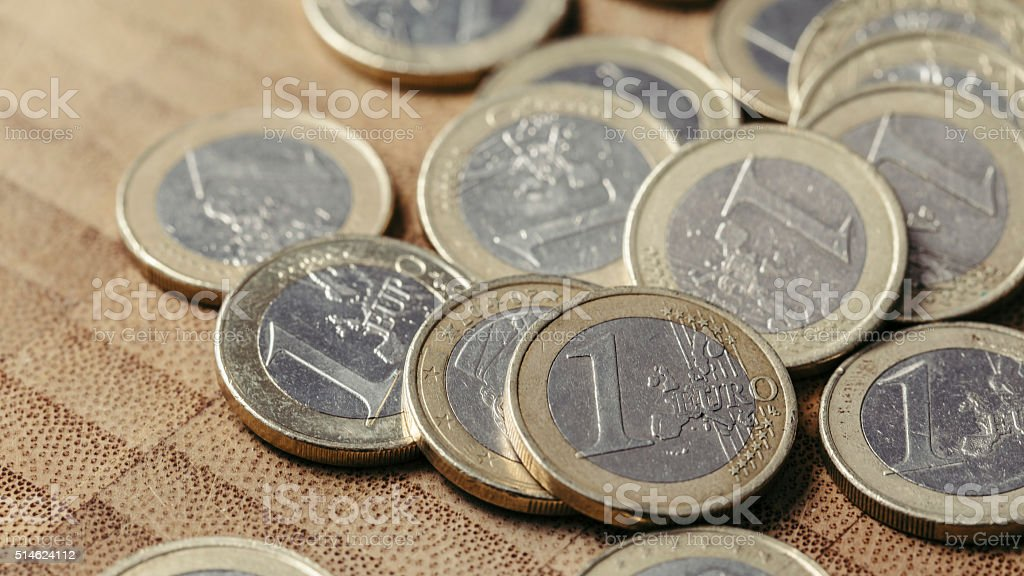 Many euro coins close up on a wooden background stock photo