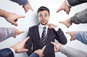 istock Many fingers pointing at a businessman 911112174