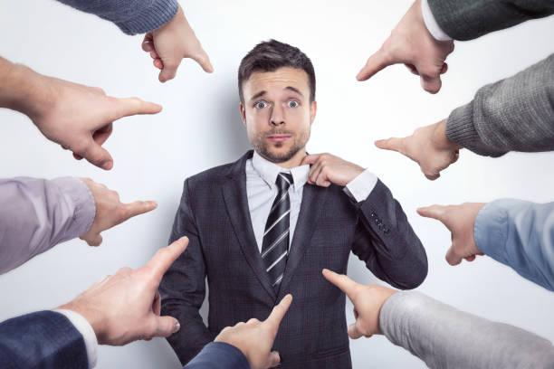 muchos dedos apuntando a un hombre de negocios - vergüenza fotografías e imágenes de stock
