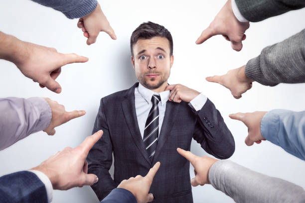 Many fingers pointing at a businessman Businessman stretching his collar while many index fingers are pointing at him. peer pressure stock pictures, royalty-free photos & images