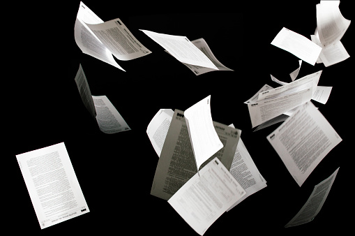Many flying business documents isolated on black background Papers flying in air in business concept