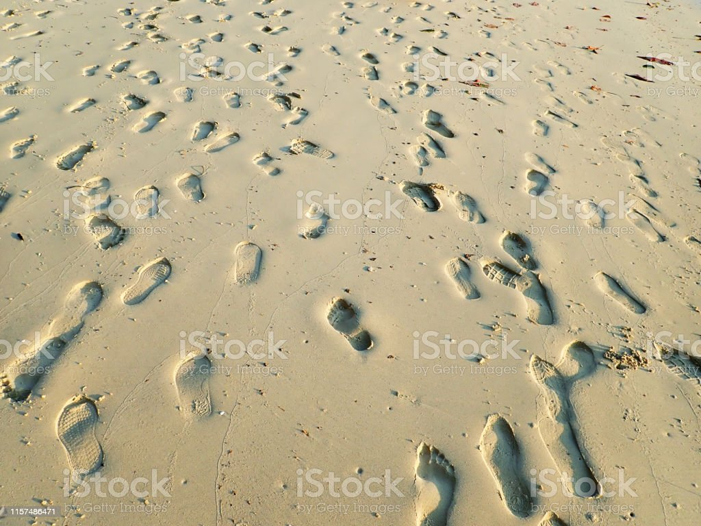 Many Footprints on the beach at sunset time.