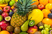 many sliced raw fruits on other colorful produce perfect background for healthy vegetarian or vegan living themes color surge trend