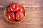 istock Many fresh red tomatoes in a woven basket close-up 1222610468