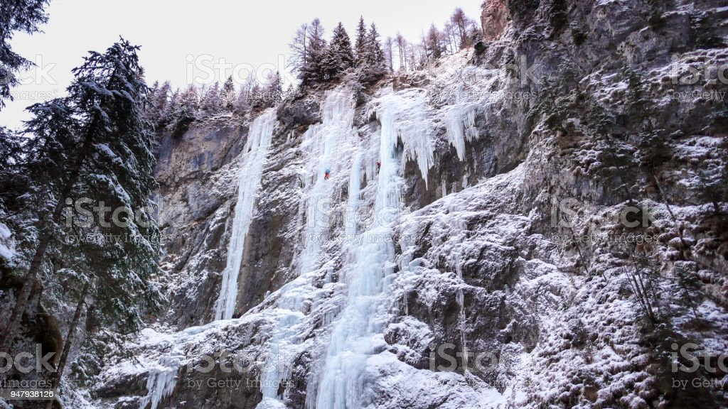 many frozen waterfalls with extreme ice climbers on them on a cold winter day in the Dolomites in Italy stock photo