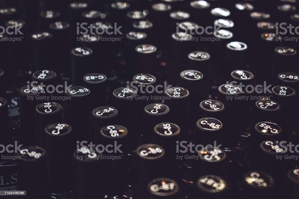 Many gel nail polishes in black bottles background. Materials for gel...