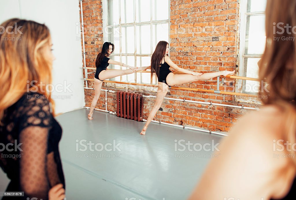 Many girls training in studio ballet, long woman legs sexy stock photo