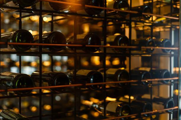 viele wein glasflaschen auf weinregale mit beleuchtung. interieur im restaurant. farbfoto - weinkeller bauen stock-fotos und bilder
