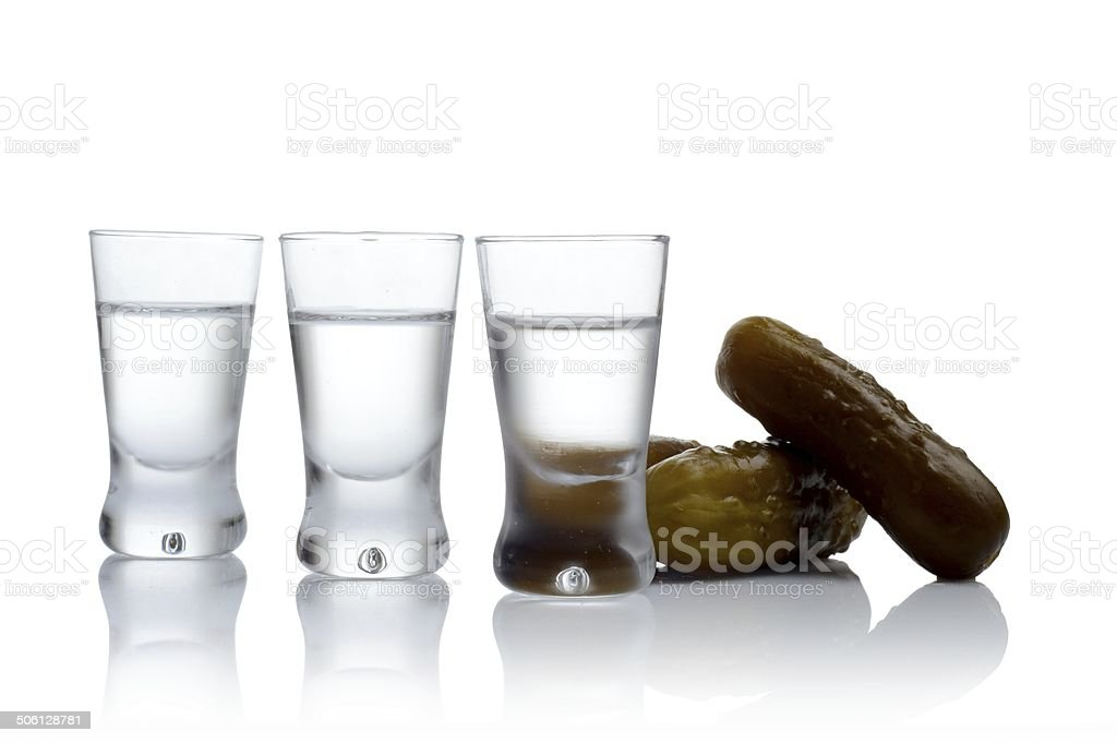 Many glasses of vodka with pickled cucumbers isolated white background stock photo