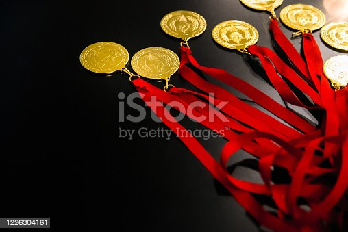 Many gold medals on a table for the victors of their challenges and inspiring goals.