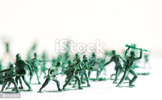 istock Many green army plastic toy soldiers organized on top of a white surface and background, isolated, with out of focus plastic soldiers in the background 867926004