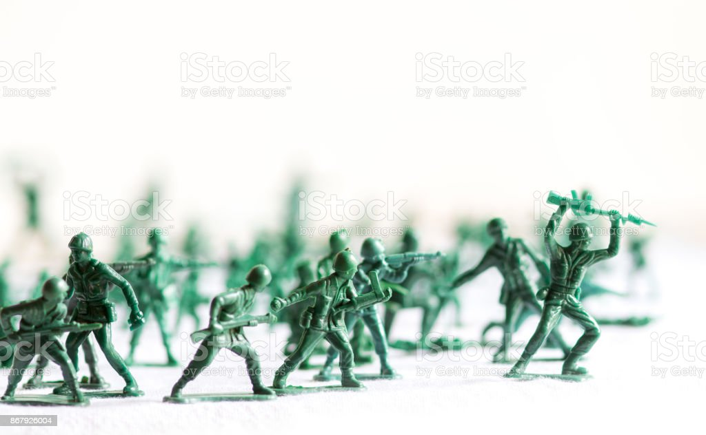 Many green army plastic toy soldiers organized on top of a white surface and background, isolated, with out of focus plastic soldiers in the background stock photo