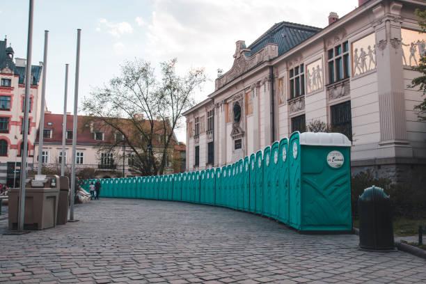 viele grüne biotoilets stehen nebeneinander auf dem platz der alten stadt - mülltonnenhäuschen stock-fotos und bilder