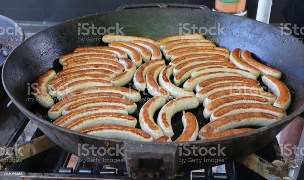Many grilled sausages, austrian bratwursts , in a large black pan in a street food shop stock photo