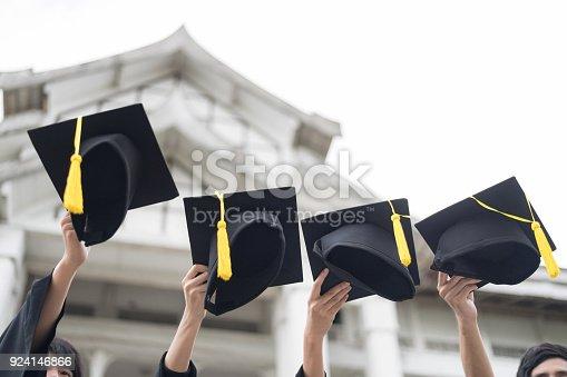 istock Many hand holding Row of graduation hats on Sky background. 924146866