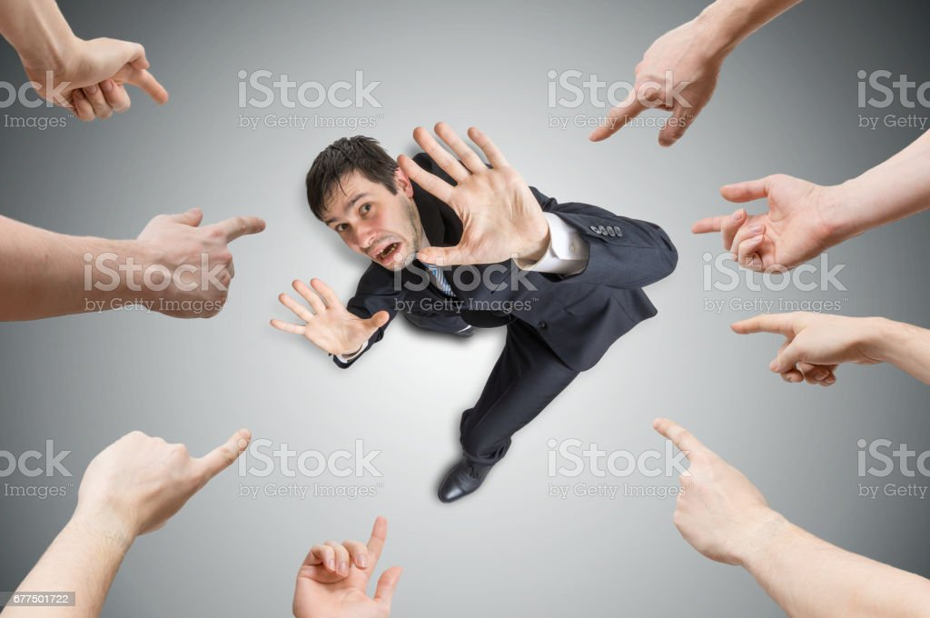 Muitas mãos estão apontando e culpam o homem estressado. Vista de cima. - foto de acervo