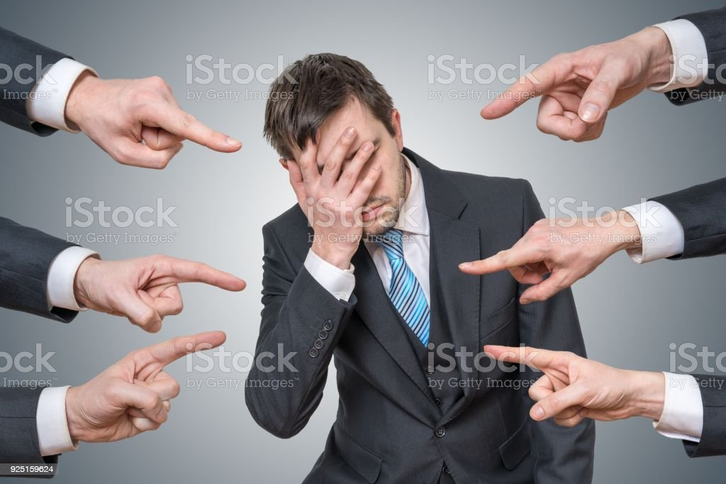 Many hands are pointing at man and blame him. stock photo