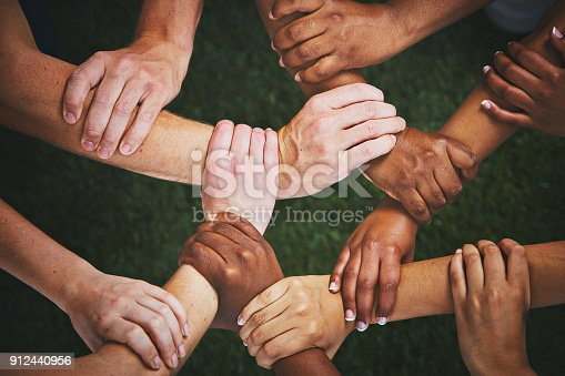 Looking down at many mixed hands, each clasping the wrist of another person and forming an interlinked human chain or mesh.