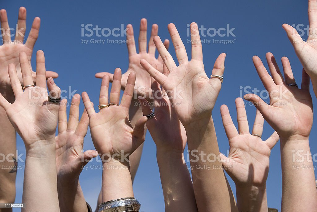 Many hands extended upward aganst blue sky royalty-free stock photo