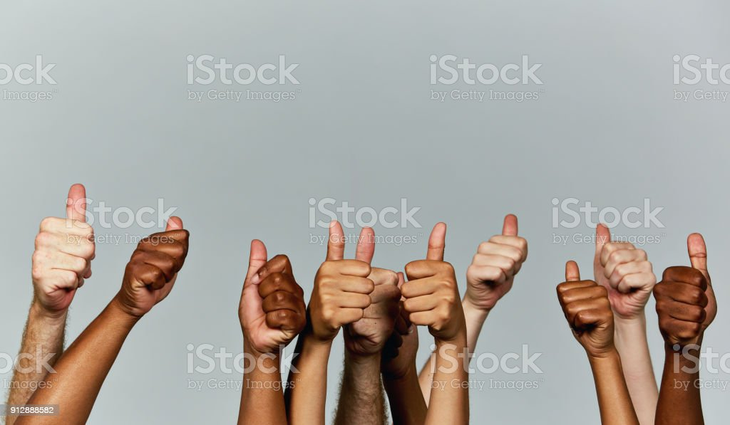 Many hands giving enthusiastic thumbs-up signals against gray background stock photo