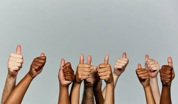many hands giving enthusiastic thumbs-up signals against gray background - thumbs up стоковые фото и изображения