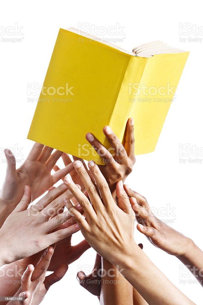 Many hands grabbing for yellow book. Isolated on white. royalty-free stock photo