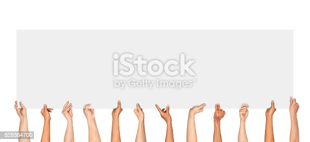 istock Many hands holding a blank poster 525364700