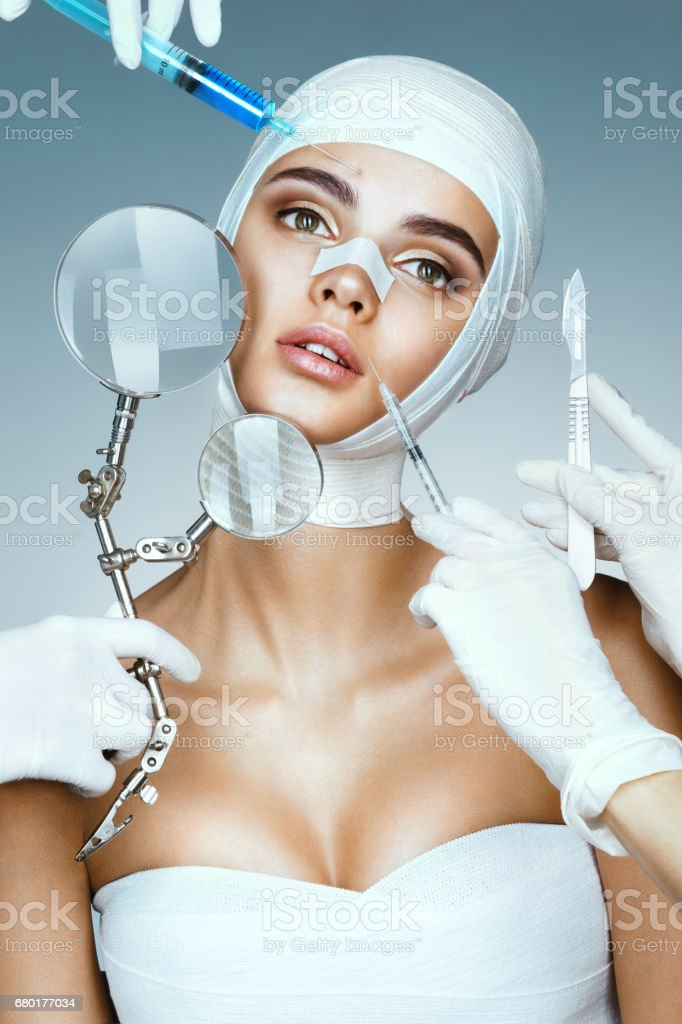 Many hands holding medical instruments near face patient stock photo