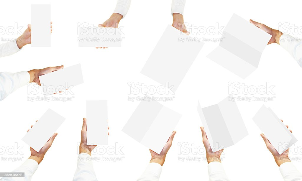 Many hands in white shirt holding blank brochure flyers stock photo
