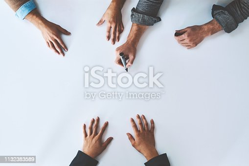 Studio shot of a group of unrecognisable people having a meeting against a white background