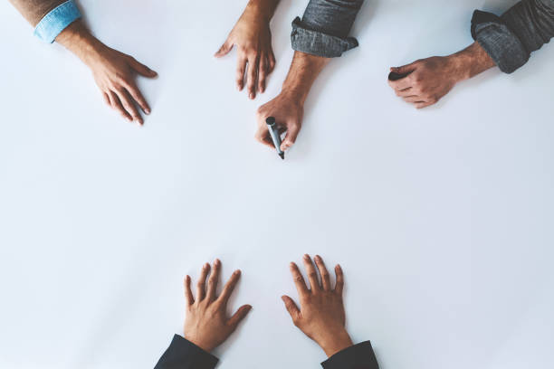 Many hands make the idea work Studio shot of a group of unrecognisable people having a meeting against a white background brainstorming stock pictures, royalty-free photos & images