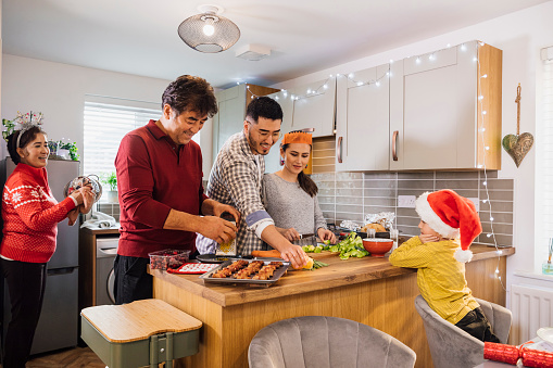 Grandparents come for Christmas and everyone is helping in the kitchen to prepare and cook the dinner. Their grandson wearing a Santa hat happily watches as they all work together.