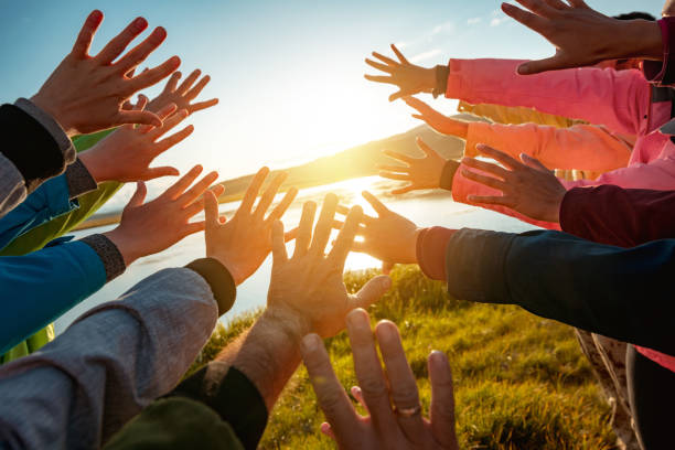 Many hands of friends reaching for the sun