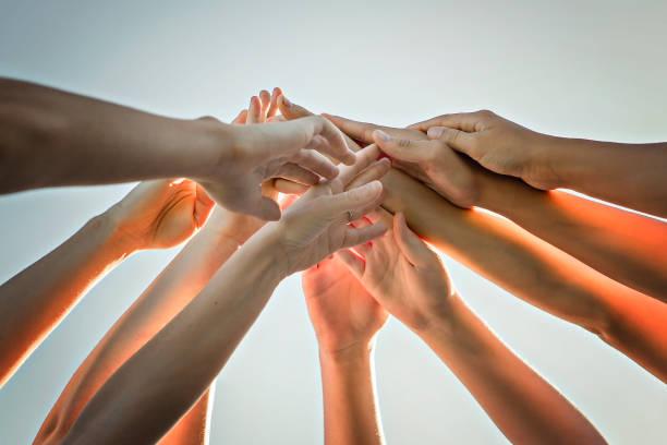 many hands over a nice sky, team work stock photo