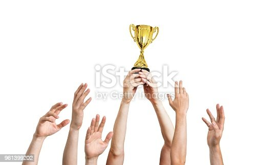 istock Many hands raised up. Winner is holding trophy in hands. Isolated on white background. 961399202