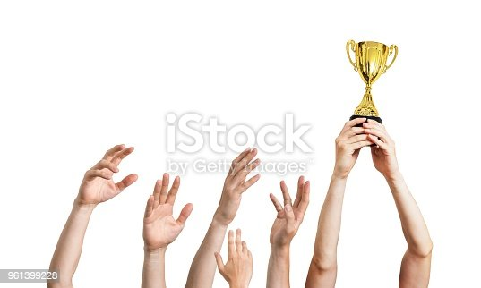 istock Many hands raised up. Winner is holding trophy in hands. Isolated on white background. 961399228