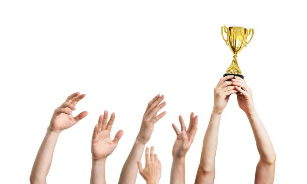 Many hands raised up. Winner is holding trophy in hands. Isolated on white background. stock photo