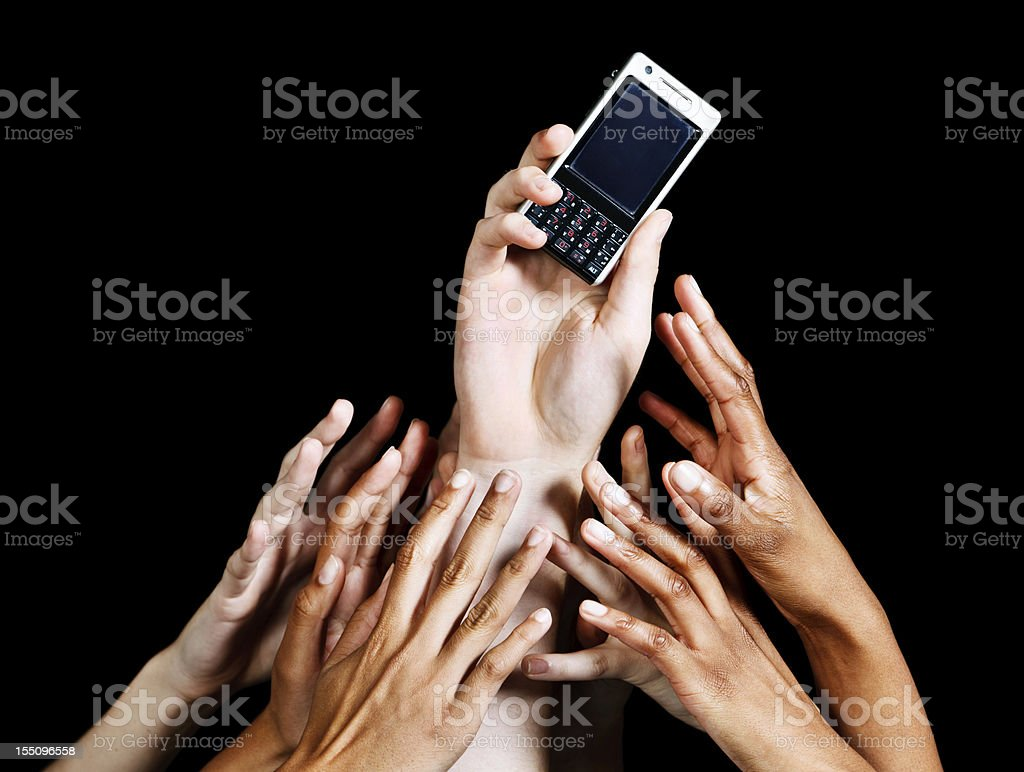 Many hands reach up against black for cellphone one holds royalty-free stock photo