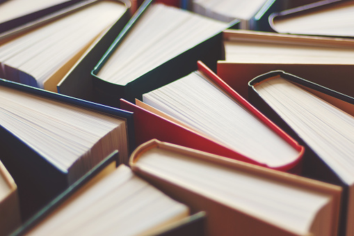 Many hardbound books background, selective focus