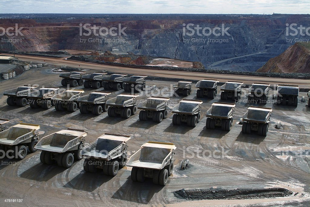 Many haul trucks parked in rows at a minesite. stock photo