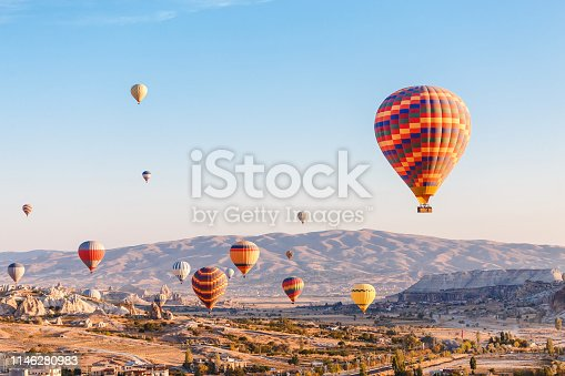 Many Hot air balloons flying over rocky landscape in Goreme city at Cappadocia, Turkey