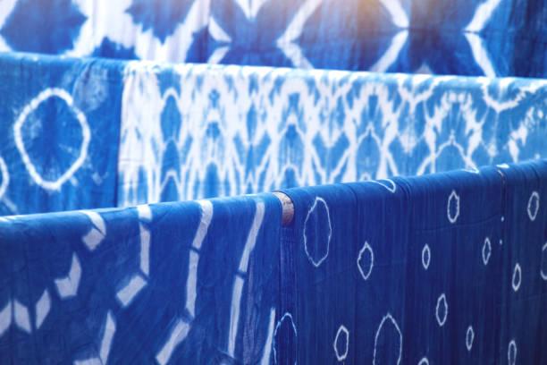 many indigo dyed fabrics, dried at the clothesline background stock photo