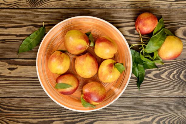 Many juicy beautiful amazing nice peaches on dark wooden background. stock photo