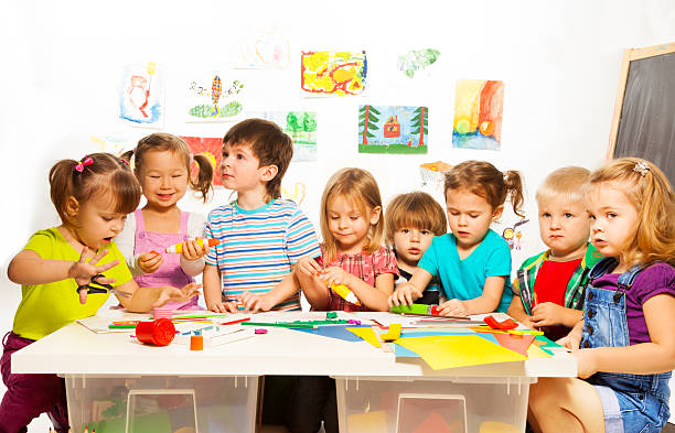 Many kids drawing and gluing stock photo