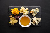 istock Many kinds of cheese with honey on stone plate on black background 1140397651