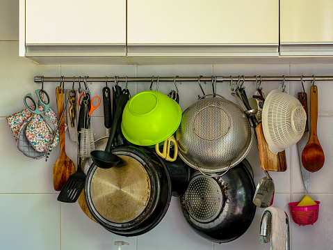 Many kitchen utensils, grungy pots and pans draining, hanging from hooks from an overloaded rail in a modern kitchen.
